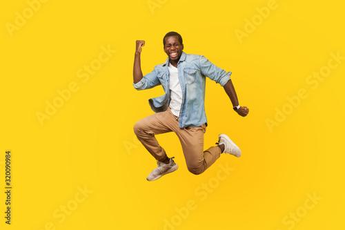 Fototapeta Full length portrait of joyous ecstatic man in denim shirt jumping for joy or flying with raised hand, gesturing yes i did it, celebrating success. indoor studio shot isolated on yellow background obraz