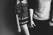 Midsection Of Couple Holding Hands While Standing Against Wall