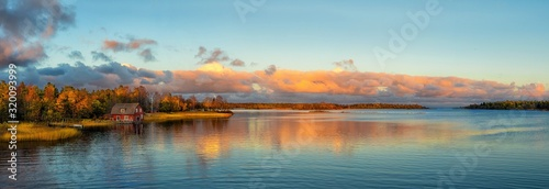 Fotografie, Obraz Scenic View Of House Beside River Against Cloudy Sky