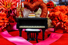Miniature Piano On Red With Va...