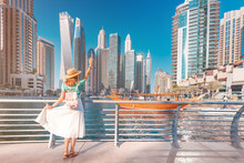 Cheerful Asian Traveler Girl Walking On A Promenade In Dubai Marina District. Travel Destinations And Tourist Lifestyle In UAE