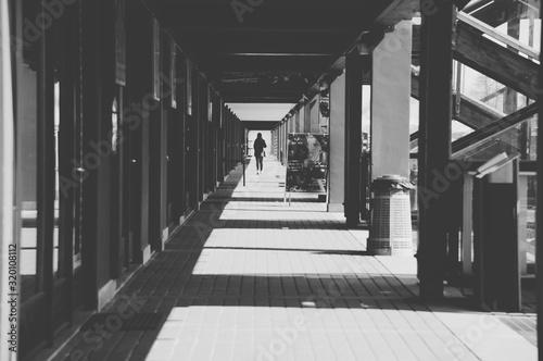 Obraz Rear View Of Woman Walking In Colonnade - fototapety do salonu