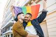 Leinwandbild Motiv Gay couple embracing and showing their love with rainbow flag.