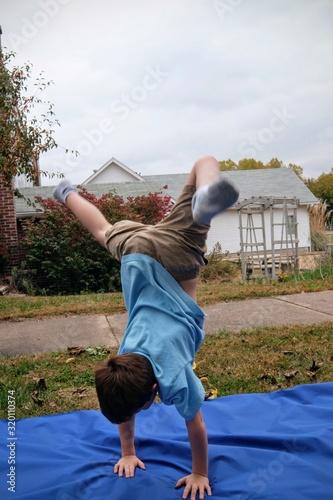 Fotografie, Tablou Boy Doing Handstand On Picnic Blanket In Park