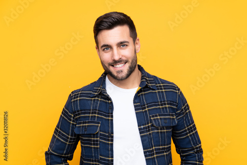 Obraz Young handsome man with beard over isolated yellow background laughing - fototapety do salonu