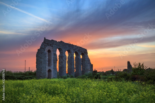 Obraz na plátně Ancient Roman Aqueduct On Field Against Sky During Sunset