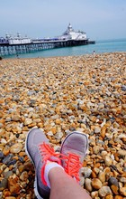 Low Section Of Woman Relaxing At Beach Against Eastbourne Pier