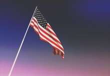 Low Angle View Of American Flag Waving Against Sky During Sunset