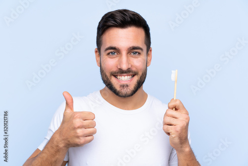 Young handsome man with beard brushing his teeth over isolated background with thumbs up because something good has happened