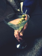 High Angle View Of Person Holding Martini With Olives At Home