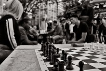 Chess Board On Table Against People