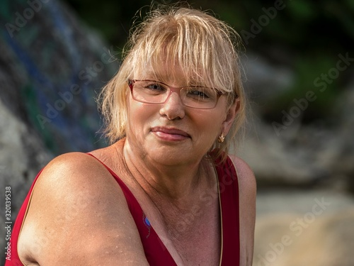 Close-up portrait of smiling mature woman with eyeglasses Wallpaper Mural