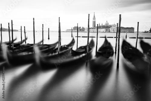 Fototapeta Gondolas Moored By Wooden Post At Grand Canal Against Sky obraz na płótnie