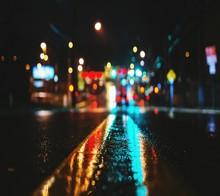 CLOSE-UP OF WET ILLUMINATED ROAD AT NIGHT