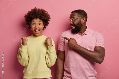 Happy black man with thick beard points at triumphing woman with clenched fists, celebrates success, exclaims joyfully, expresses positive emotions Canvas Print