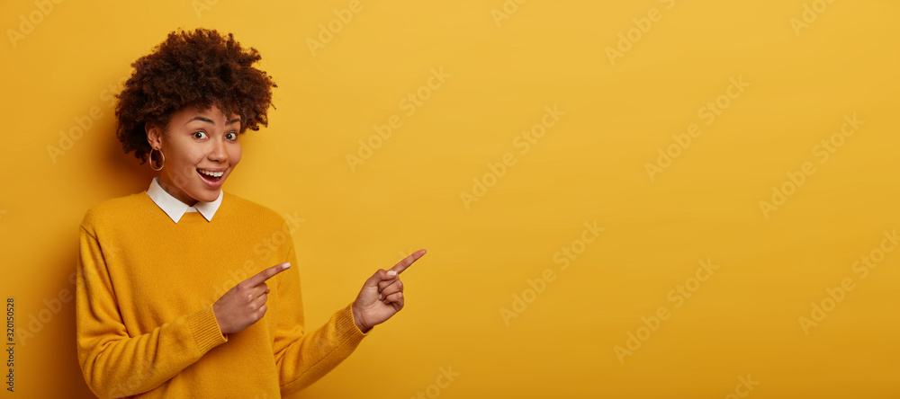 Fototapeta Cute happy woman wears yellow sweater, points both index fingers aside, demonstrates copy space for your information or promotion, gives direction to huge mall, isolated over vivid studio wall