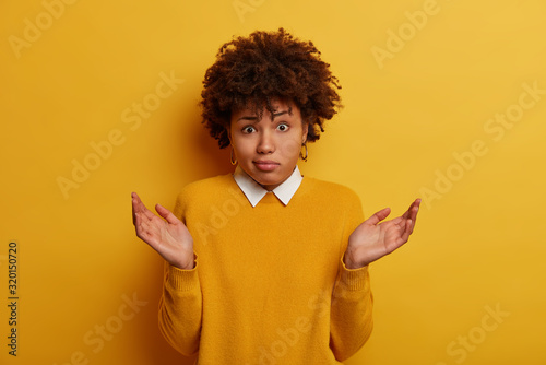 Photo Puzzled questioned Afro American woman raises hands sideways, stands hesitant, expresses doubts, wears yellow sweater, says I dont know, cant help, makes decision, shakes unaware