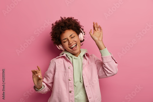 Obraz Joyful curly haired teenage girl dances carefree listens audio track in headphones, enjoys playlist, sings song along, wears casual apparel, poses against pink pastel background, expresses happiness - fototapety do salonu
