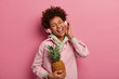canvas print picture - Energized woman laughs happily, has positive expression, listens stereo headphones, enjoys music in playlist, holds pineapple, wears sweatshirt, isolated over pink wall has fun stands with closed eyes