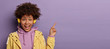 canvas print picture - Millennial hipster girl with Afro hair enjoys music podcast in headphones, points fore finger on copy space for your advertising, has excited surprised happy expression, isolated on purple background