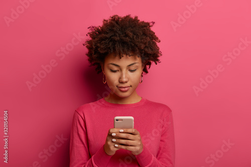 Fototapeta Photo of serious curly woman uses modern device, orders taxi via smartphone application, texts or browses in social media, wears bright crimson clothes, isolated on pink background, checks email box obraz