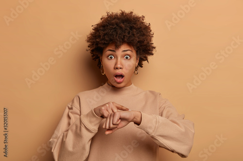 Fototapeta Frightened woman worries about deadline, makes time gesture, being late for important meeting, drops jaw and has bugged eyes, wears sweatshirt, isolated over brown background. Omg, be hurry! obraz