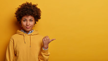 Recommend You To Use Copy Space. Calm Lovely Afro American Woman Points Thumb Aside, Shows Nice Place To Visit, Wears Hoodie, Isolated On Yellow Studio Background, Suggets Good Offer Or Proposal
