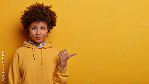 Obraz Recommend you to use copy space. Calm lovely Afro American woman points thumb aside, shows nice place to visit, wears hoodie, isolated on yellow studio background, suggets good offer or proposal - fototapety do salonu