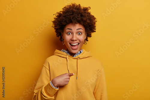 Photo Joyful teenage girl points at herself, happy to be chosen to participate in inte
