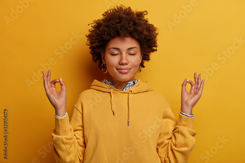 Portrait of ethnic woman stays calm, meditates and practices yoga, keeps hands in zen gesture, closes eyes, relaxes after hard working day, wears yellow sweatshirt, poses indoor, unites with nature