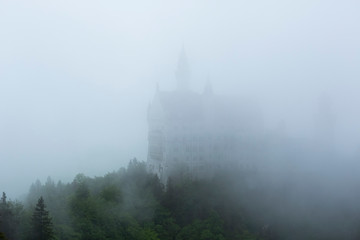 Neuschwanstein Castle on a foggy day, only a shadows are visible,