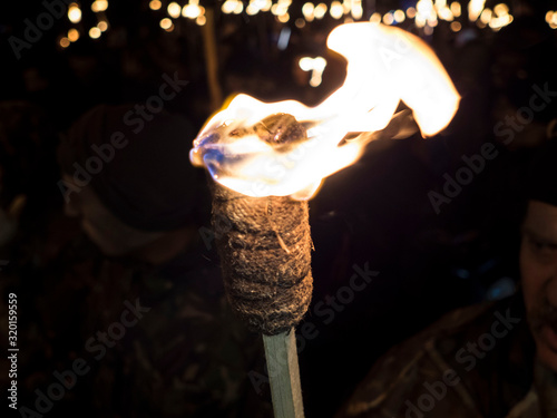Fotografiet Cropped Image Of Man With Flaming Torch During Procession At Night