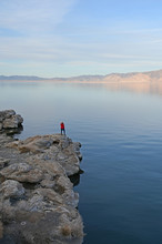 Young Woman In Red Sweater And Jeans Enjoying View Of Pyramid Lake, Nevada From Rock Formations On Coast On Late Winter Afternoon.