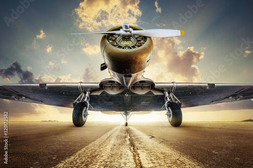 historical aircraft on a runway  against  a sunset Fototapet