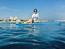 Smiling Woman Sitting On Paddleboard In Sea Against Sky