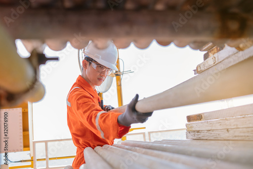 Fotografie, Obraz Scaffolder pulling scaffolding on pipe rack for construction work on offshore oil and gas processing platform