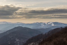 Moody, Dramatic Sky Above Pointy, Distant, Impressive Kom Summit In Bulgaria Covered By Snow And Misty, Foreground Mountain Layers