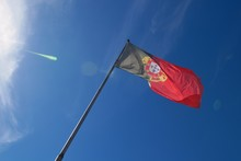 Low Angle View Of Portuguese Flag Against Blue Sky