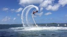 Man Flyboarding Over Sea Against Sky