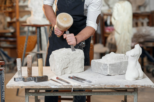 Fotografiet Bearded craftsman works in white stone carving with a chisel