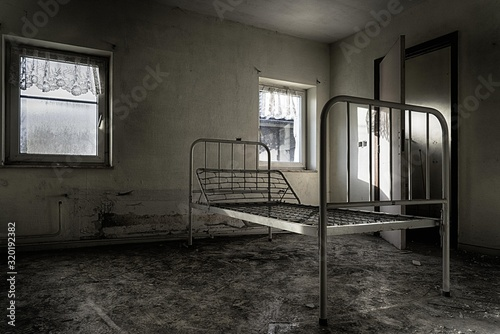 Dramatic shot of an abandoned prison room with a broken bed and weathered window Wallpaper Mural