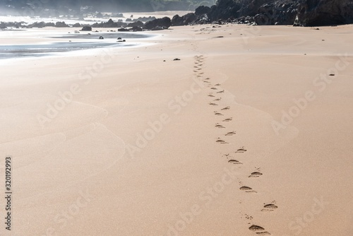 Valokuvatapetti Beautiful view of the footsteps on the beach sand near the shore with rocks in t