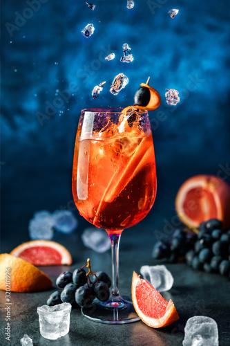Świeży grapefruitowy koktajl z pomarańcze, winogronami i lodem w wineglass na zmroku - błękitny tło. Strzał studio napoju w zamrożonym ruchu, latający lód, krople w plusk cieczy. Letni zimny napój i koktajl