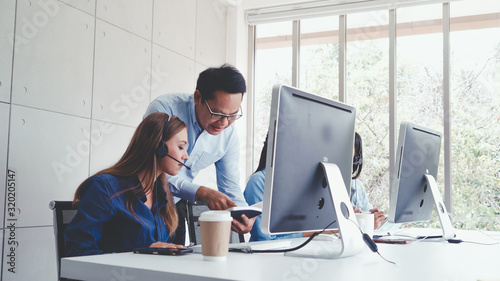 Fotomural Customer support agent or call center with headset works on desktop computer while supporting the customer on phone call