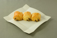 Three Breakfast Chocolate Mini Croissant Pastries On White Plate On Grey Tablecloth
