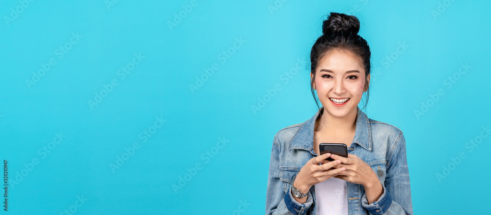 Fototapeta Banner of Portrait happy asian woman feeling happiness and looking camera holding smartphone on blue background. Cute asia girl smiling wearing casual jeans shirt and connect internet shopping online