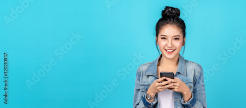 Photo Banner of Portrait happy asian woman feeling happiness and looking camera holding smartphone on blue background