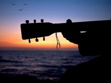 CLOSE-UP OF SILHOUETTE Of Man Playing Guitar On Beach