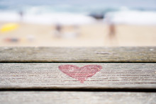 Close-Up Of Red Heart Shape On Wooden Bench