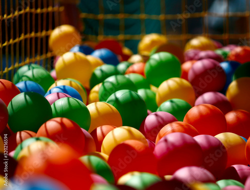 Bright background of colored plastic balls. A solar beam falls on colored balls for children's games. Side view, close-up, horizontal. The concept of childhood.